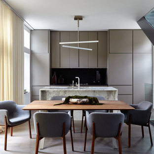 Mid-sized modern galley eat-in kitchen in New York with an undermount sink, flat-panel cabinets, grey cabinets, marble benchtops, black splashback, stone slab splashback, stainless steel appliances, with island, brown floor, multi-coloured benchtop and dark hardwood floors.