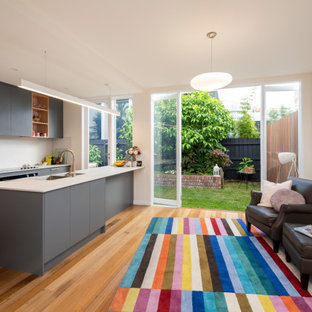 Mid-sized contemporary galley open plan kitchen in Melbourne with a drop-in sink, flat-panel cabinets, grey cabinets, granite benchtops, white splashback, stainless steel appliances, medium hardwood floors, with island, brown floor and white benchtop.