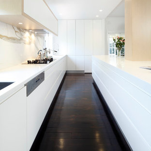 Minimalist single-wall kitchen photo in Sydney with flat-panel cabinets, white cabinets, solid surface countertops, stone slab backsplash, stainless steel appliances and an undermount sink