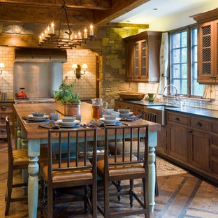 Inspiration for a large arts and crafts u-shaped eat-in kitchen in Denver with a farmhouse sink, recessed-panel cabinets, distressed cabinets, solid surface benchtops, white splashback, subway tile splashback, panelled appliances, ceramic floors, with island and brown floor.