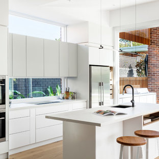 Photo of a contemporary galley open plan kitchen in Sydney with an undermount sink, flat-panel cabinets, white cabinets, window splashback, stainless steel appliances, medium hardwood floors, with island, brown floor and white benchtop.