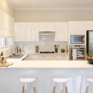 シドニーの中サイズのコンテンポラリースタイルのおしゃれなキッチン (ダブルシンク、フラットパネル扉のキャビネット、白いキャビネット、御影石カウンター、白いキッチンパネル、セラミックタイルのキッチンパネル、シルバーの調理設備の、濃色無垢フローリング) の写真