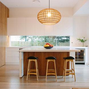 Exemple d'une cuisine tendance en L avec un placard à porte plane, des portes de placard blanches, un électroménager en acier inoxydable, un sol en bois clair et un îlot central.
