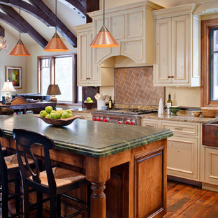 Design ideas for a mid-sized traditional l-shaped open plan kitchen in Denver with a farmhouse sink, recessed-panel cabinets, beige cabinets, stainless steel appliances, medium hardwood floors, with island, marble benchtops, brown splashback, stone tile splashback, brown floor and green benchtop.