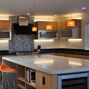Design ideas for a mid-sized modern l-shaped eat-in kitchen in San Francisco with flat-panel cabinets, light wood cabinets, black splashback, stainless steel appliances, with island, a drop-in sink, quartz benchtops, ceramic splashback, cement tiles and grey floor.