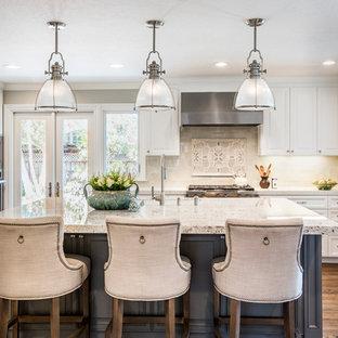 Exempel på ett stort klassiskt l-kök, med en rustik diskho, luckor med profilerade fronter, vita skåp, granitbänkskiva, vitt stänkskydd, stänkskydd i porslinskakel, rostfria vitvaror, mellanmörkt trägolv och en köksö