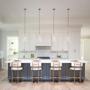 Design ideas for a large country l-shaped open plan kitchen in San Francisco with a farmhouse sink, shaker cabinets, white cabinets, quartz benchtops, white splashback, ceramic splashback, stainless steel appliances, light hardwood floors, with island, grey floor, white benchtop and recessed.