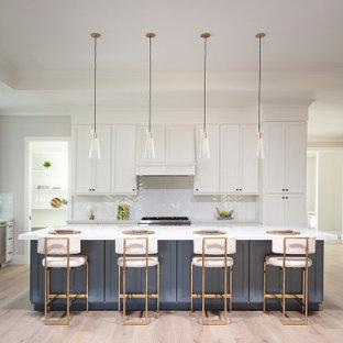 Foto på ett stort lantligt vit kök, med en rustik diskho, skåp i shakerstil, vita skåp, bänkskiva i kvarts, vitt stänkskydd, stänkskydd i keramik, rostfria vitvaror, ljust trägolv, en köksö och grått golv
