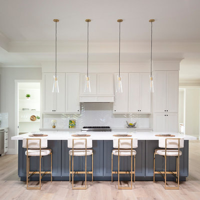 Example of a large farmhouse l-shaped light wood floor, gray floor and tray ceiling open concept kitchen design in San Francisco with a farmhouse sink, shaker cabinets, white cabinets, quartz countertops, white backsplash, ceramic backsplash, stainless steel appliances, an island and white countertops