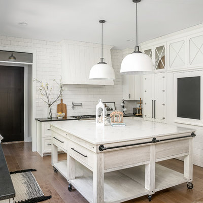 Kitchen - country u-shaped medium tone wood floor and brown floor kitchen idea in Chicago with a farmhouse sink, shaker cabinets, white cabinets, white backsplash, subway tile backsplash and an island