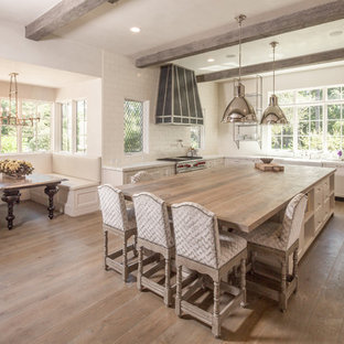 This is an example of a large shabby-chic style u-shaped eat-in kitchen in Houston with a farmhouse sink, shaker cabinets, white cabinets, solid surface benchtops, white splashback, ceramic splashback, stainless steel appliances, medium hardwood floors, with island and brown floor.