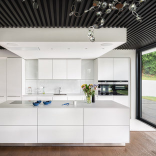 Design ideas for a large contemporary galley open plan kitchen in London with a submerged sink, flat-panel cabinets, white cabinets, white splashback, glass sheet splashback, integrated appliances, medium hardwood flooring, an island, beige floors and white worktops.