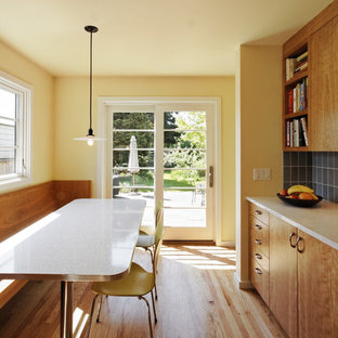 Transitional galley eat-in kitchen photo in Portland with flat-panel cabinets, medium tone wood cabinets, blue backsplash, recycled glass countertops, ceramic backsplash, a farmhouse sink and stainless steel appliances