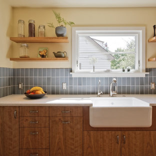 This is an example of a transitional galley eat-in kitchen in Portland with a farmhouse sink, blue splashback, flat-panel cabinets, medium wood cabinets, recycled glass benchtops, ceramic splashback and stainless steel appliances.