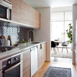 ロサンゼルスのコンテンポラリースタイルのおしゃれな独立型キッチン (アンダーカウンターシンク、フラットパネル扉のキャビネット、茶色いキャビネット、黒いキッチンパネル、コルクフローリング、アイランドなし、茶色い床) の写真