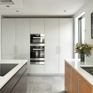 Design ideas for a large contemporary single-wall kitchen/diner in London with a double-bowl sink, flat-panel cabinets, white splashback, stainless steel appliances, an island, grey floors, white worktops, light wood cabinets, composite countertops and ceramic flooring.