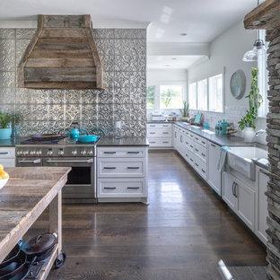 Große Landhaus Küche in L-Form mit Landhausspüle, Schrankfronten im Shaker-Stil, weißen Schränken, Quarzwerkstein-Arbeitsplatte, Küchenrückwand in Metallic, Rückwand aus Metallfliesen, Küchengeräten aus Edelstahl, braunem Boden, grauer Arbeitsplatte und dunklem Holzboden in Nashville