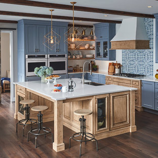 This is an example of a beach style l-shaped kitchen in Austin with a belfast sink, recessed-panel cabinets, blue cabinets, blue splashback, mosaic tiled splashback, dark hardwood flooring, an island, brown floors and white worktops.