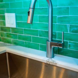 マイアミの中くらいのトロピカルスタイルのおしゃれなキッチン (アンダーカウンターシンク、中間色木目調キャビネット、クオーツストーンカウンター、緑のキッチンパネル、ガラスタイルのキッチンパネル、シルバーの調理設備、磁器タイルの床、グレーの床、マルチカラーのキッチンカウンター、落し込みパネル扉のキャビネット) の写真