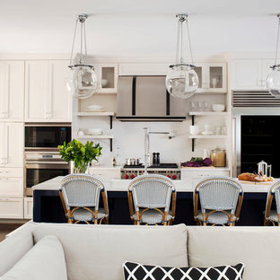 Transitional open concept kitchen remodeling - Open concept kitchen - transitional galley dark wood floor open concept kitchen idea in Atlanta with a farmhouse sink, recessed-panel cabinets, white cabinets, solid surface countertops, white backsplash, stainless steel appliances and an island