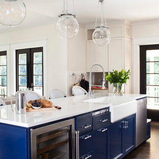Mid-sized transitional open concept kitchen designs - Inspiration for a mid-sized transitional galley dark wood floor open concept kitchen remodel in Atlanta with a farmhouse sink, recessed-panel cabinets, blue cabinets, solid surface countertops, stainless steel appliances and an island