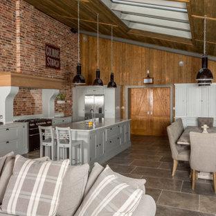 Inredning av ett lantligt stort vit vitt kök, med en köksö, en undermonterad diskho, skåp i shakerstil, grå skåp, rött stänkskydd, stänkskydd i tegel, rostfria vitvaror och grått golv