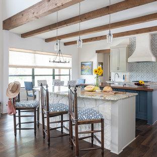 オースティンの中くらいのサンタフェスタイルのおしゃれなマルチアイランドキッチン (シェーカースタイル扉のキャビネット、御影石カウンター、濃色無垢フローリング、茶色い床、セラミックタイルのキッチンパネル、グレーのキャビネット、マルチカラーのキッチンパネル、マルチカラーのキッチンカウンター) の写真