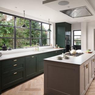Imagen de cocina de galera, tradicional renovada, abierta, con fregadero de tres senos, armarios estilo shaker, puertas de armario verdes, electrodomésticos negros, suelo de madera clara y una isla