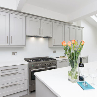 Mid-sized modern eat-in kitchen ideas - Inspiration for a mid-sized modern single-wall porcelain floor and black floor eat-in kitchen remodel in London with a drop-in sink, shaker cabinets, gray cabinets, quartzite countertops, white backsplash, glass sheet backsplash, stainless steel appliances, an island and white countertops