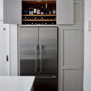 Idee per una cucina abitabile design di medie dimensioni con lavello integrato, ante in stile shaker, ante grigie, top in quarzite, paraspruzzi blu, paraspruzzi con lastra di vetro, elettrodomestici in acciaio inossidabile, parquet scuro, isola, pavimento marrone e top bianco