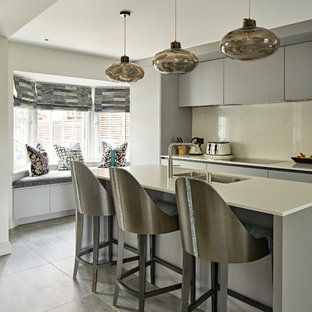 Photo of a medium sized contemporary kitchen in London with flat-panel cabinets, grey cabinets, an island, a double-bowl sink, beige splashback, grey floors and beige worktops.