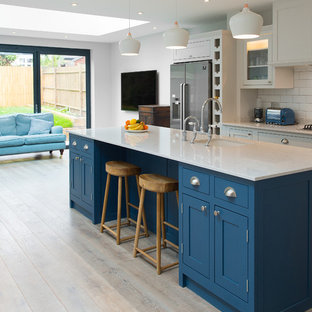 Design ideas for a medium sized traditional kitchen/diner in London with a submerged sink, shaker cabinets, blue cabinets, white splashback, metro tiled splashback, stainless steel appliances, light hardwood flooring and an island.