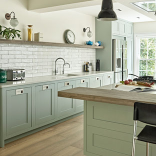 Large transitional single-wall open plan kitchen in London with a drop-in sink, shaker cabinets, green cabinets, quartzite benchtops, white splashback, subway tile splashback, stainless steel appliances, with island and white benchtop.