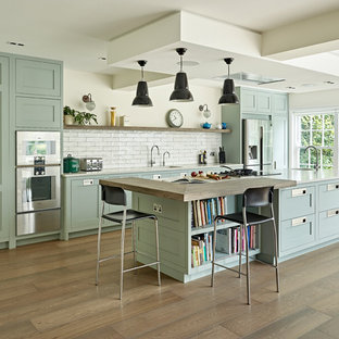 Photo of a large transitional single-wall open plan kitchen in London with a drop-in sink, shaker cabinets, green cabinets, quartzite benchtops, white splashback, subway tile splashback, stainless steel appliances, with island and white benchtop.