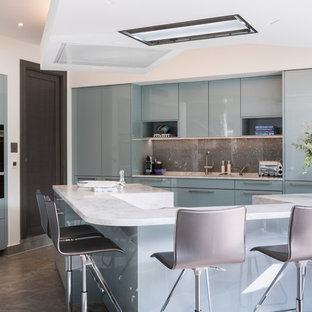 Inspiration for a mid-sized contemporary l-shaped eat-in kitchen in London with a drop-in sink, flat-panel cabinets, blue cabinets, solid surface benchtops, metallic splashback, glass sheet splashback, black appliances, ceramic floors, with island, brown floor and beige benchtop.