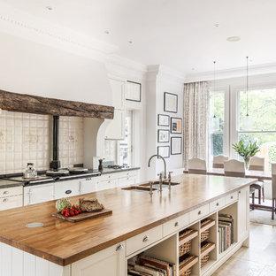 ロンドンのカントリー風おしゃれなキッチン (ダブルシンク、落し込みパネル扉のキャビネット、白いキャビネット、木材カウンター、白いキッチンパネル、白い調理設備、トラバーチンの床、白い床) の写真