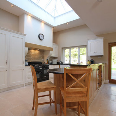 Example of a trendy kitchen design in Hampshire with shaker cabinets and black appliances