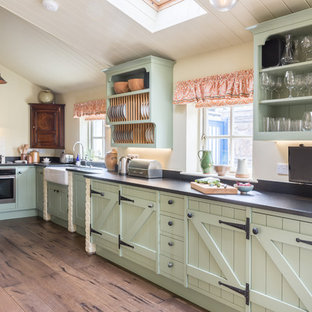 Immagine di una cucina in campagna con lavello stile country, ante a persiana, ante verdi, elettrodomestici neri, pavimento in legno massello medio, nessuna isola e pavimento marrone