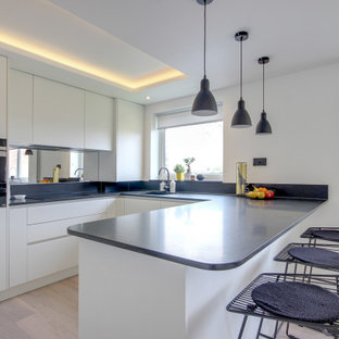 Photo of a mid-sized contemporary u-shaped open plan kitchen in London with an integrated sink, flat-panel cabinets, white cabinets, granite benchtops, metallic splashback, glass sheet splashback, a peninsula and black benchtop.
