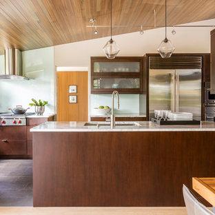 Modelo de cocina comedor rural con fregadero bajoencimera, armarios tipo vitrina, puertas de armario de madera en tonos medios, salpicadero de vidrio templado, electrodomésticos de acero inoxidable, península y suelo marrón