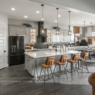Esempio di una cucina abitabile classica con lavello sottopiano, ante in stile shaker, ante grigie, paraspruzzi grigio, paraspruzzi con piastrelle diamantate, elettrodomestici neri, isola, pavimento grigio e top bianco
