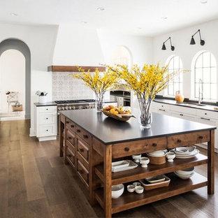 ジャクソンビルの広い地中海スタイルのおしゃれなキッチン (アンダーカウンターシンク、シェーカースタイル扉のキャビネット、白いキャビネット、ソープストーンカウンター、マルチカラーのキッチンパネル、セラミックタイルのキッチンパネル、パネルと同色の調理設備、濃色無垢フローリング、茶色い床、黒いキッチンカウンター) の写真