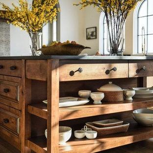 ジャクソンビルの大きい地中海スタイルのおしゃれなキッチン (アンダーカウンターシンク、シェーカースタイル扉のキャビネット、白いキャビネット、ソープストーンカウンター、マルチカラーのキッチンパネル、セラミックタイルのキッチンパネル、パネルと同色の調理設備、濃色無垢フローリング、茶色い床、黒いキッチンカウンター) の写真