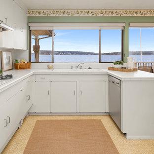 シアトルの大きいミッドセンチュリースタイルのおしゃれなキッチン (フラットパネル扉のキャビネット、白いキャビネット、タイルカウンター、白いキッチンパネル、磁器タイルのキッチンパネル、シルバーの調理設備の、ラミネートの床、茶色い床、白いキッチンカウンター) の写真