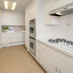シアトルの広いミッドセンチュリースタイルのおしゃれなキッチン (フラットパネル扉のキャビネット、白いキャビネット、タイルカウンター、白いキッチンパネル、磁器タイルのキッチンパネル、シルバーの調理設備、ラミネートの床、茶色い床、白いキッチンカウンター) の写真