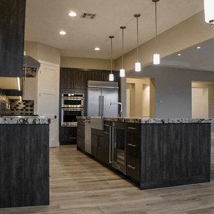 Cette photo montre une grande cuisine ouverte parallèle tendance avec un placard à porte shaker, des portes de placard en bois sombre, un plan de travail en granite, une crédence en carreau de céramique, un électroménager en acier inoxydable, un sol en carrelage de porcelaine, un îlot central, un sol gris et un évier 3 bacs.
