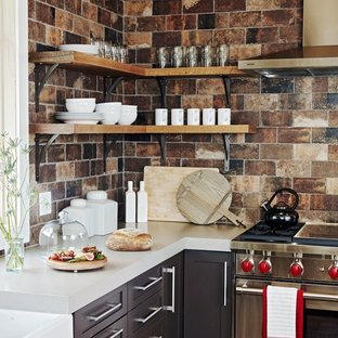 Rustic kitchen pictures - Inspiration for a rustic l-shaped kitchen remodel in New York with a farmhouse sink, shaker cabinets, brown cabinets, multicolored backsplash, stainless steel appliances and gray countertops