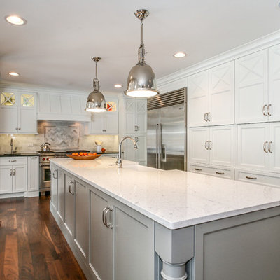 Inspiration for a large timeless u-shaped dark wood floor and brown floor kitchen remodel in Chicago with a farmhouse sink, shaker cabinets, white cabinets, white backsplash, stainless steel appliances, quartzite countertops and an island