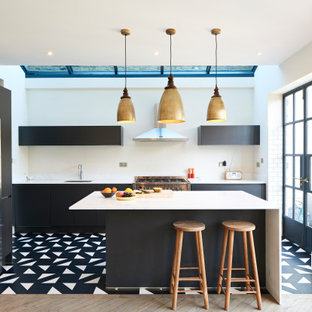 Contemporary l-shaped kitchen in London with a submerged sink, flat-panel cabinets, black cabinets, white splashback, white appliances, an island and multi-coloured floors.