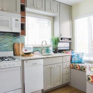 Idéer för att renovera ett litet maritimt linjärt kök med öppen planlösning, med en undermonterad diskho, grå skåp, grönt stänkskydd, vita vitvaror, skåp i shakerstil, granitbänkskiva, glaspanel som stänkskydd, vinylgolv och brunt golv